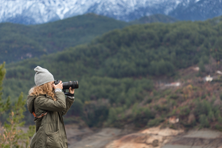 Horizontal sideview portrait of a blonde photogrpher woman wearing khaki parka and gray hat photographing mountains using long focal length lens