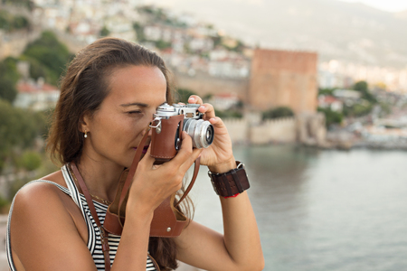 Head and shoulders portrait of a traveller woman photographing using vintage film camera and standing against the blurred backdrop of Alanya bay in Turkey and Red Tower.