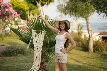 Young female with long straight hair, wearing white top and beige shorts holding a pice of macrame wall art in her hand and smiling, shot with shallow depth of field