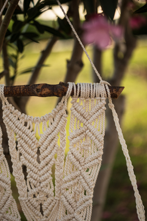 Closeup of macrame art hanging from the piece of driftwood, shot with shallow depth of field