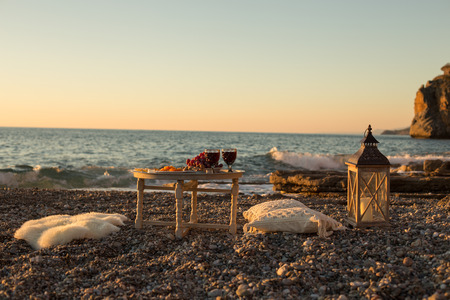 Romantic outdoor dinner with wine and cheese by seaside. Two glasses of wine, grapes, dried fruits and cheese placed on small round table, with white pillows and sheepskin around the table.