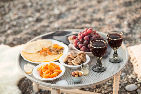 ourdoor picnic with two glasses of red wine, olives, cheese, dried froots, candles and seashells placed on round metal coffee table