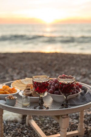 Romantic outdoor dinner with wine and cheese by seaside. Two glasses of wine, grapes and dried fruits on rustic round metal table. Vertical composition. Copy space.