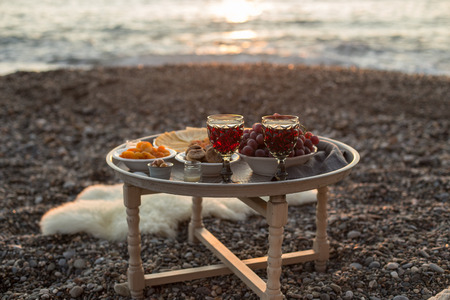 Romantic outdoor dinner with wine and cheese by seaside. Two glasses of wine, grapes, olives and dried fruits on rustic round metal table. Vertical composition.