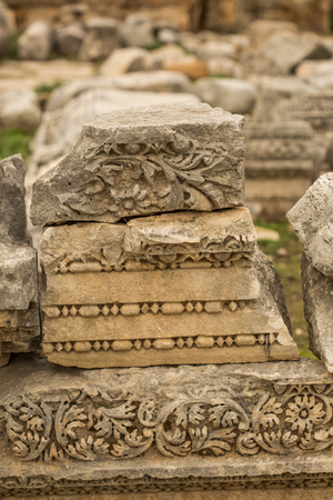 Old carved stones in ancient town of Perge in Turkey. Laying on top of each other. Stock Photo