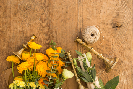 Topview shot of yellow ranunculus, white lisianthus, eucalyptus, vintage candleholders on wooden rustic tabletop
