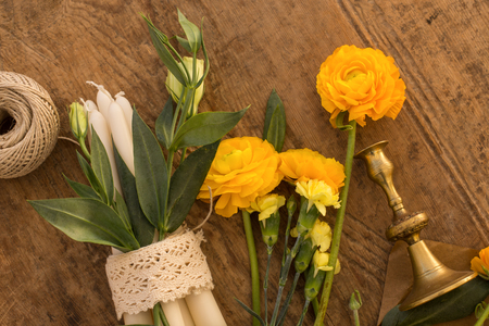 Topview shot of yellow ranunculus, white lisianthus, eucalyptus, vintage candleholders on wooden rustic tabletop. Stock Photo
