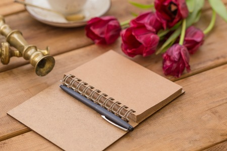 Notepad with black pen on wooden tabletop with purple tulips and vintage candleholder blurred at background.