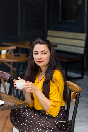Female with long dark hair, wearing yellow shirt, brown polka dot skirt and red lipstick drinking cappuccino in a coffee shop with dark interior. Vertical composition.