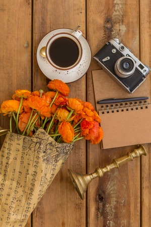 Writing in spring concept. Upper view shot of orange ranunculus, vintage candleholder and film camera, a cup of black coffee and notepad with pen on wooden tabletop.