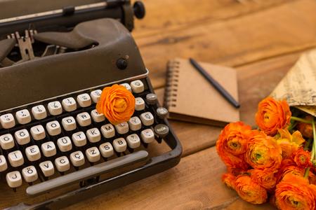 Writing in spring. Retro typewriter, orange ranunculus and notepad on wooden tabletop. Stock Photo