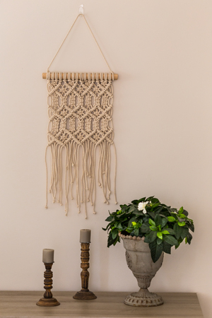 Interior decoration concept. Macrame wall art, wooden candleholders and gardenia flower in metal vase. Vertical composition.