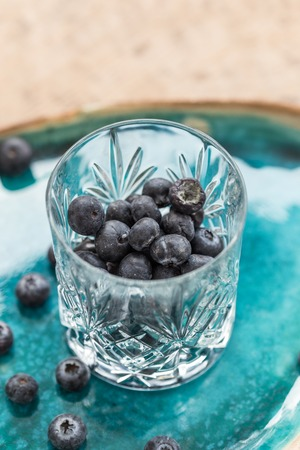 Healthy eating. Blueberries in crystall glass placed on turquoise ceramic plate. Vertical composition, shot with shallow depth of field.