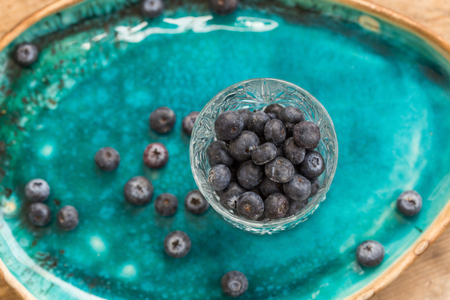 Healthy eating. Blueberries in crystall glass placed on turquoise ceramic plate. Top view depth of field.