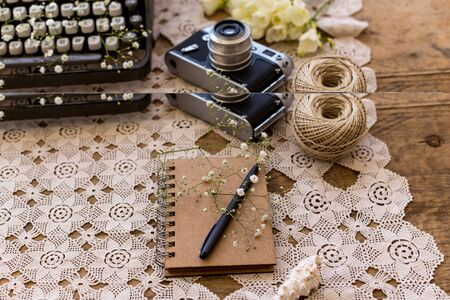 Spring or summer freelance, business or writing concept. Notepad with black pen on lace table cover with vintage film camera and retro typewriter blurred at distance view. Stock Photo