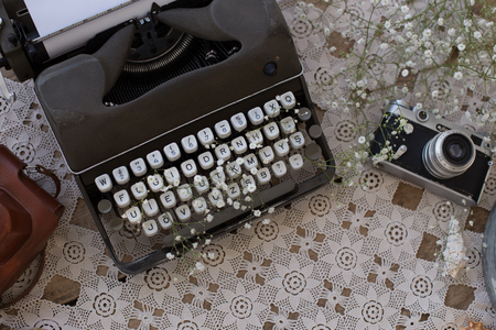 Spring or summer freelance and writing concept. Dark gray retro typewriter with gypsophila in its white keys and vintage film camera on lace table cover. Copy space.