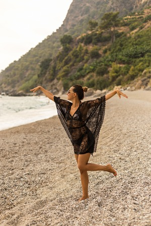 Vertical full lengh portrait of young woman wearing black lace tunic and dancing in a beautiful bay.