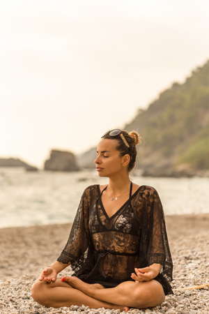 Female wearing black lace tunic meditating in a beautiful bay.  Vertical shot. Copy space.