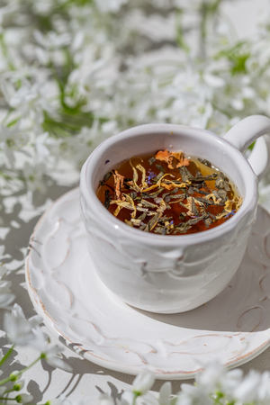 Vertical shot of a white rustic cup with herbal tea surrounded by flowers. Shot with shallow depth of field and under harsh light conditions.