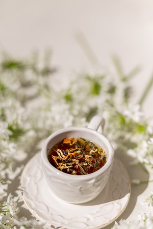 Vertical shot of a white rustic cup with herbal tea surrounded by flowers. Shot with shallow depth of field and under harsh light conditions. Copy space.