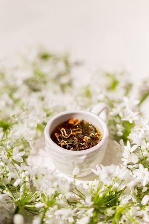 Disparo vertical de una taza rústica blanca con té de hierbas rodeado de flores. Filmada con poca profundidad de campo y bajo duras condiciones de luz. Copie el espacio. Foto de archivo