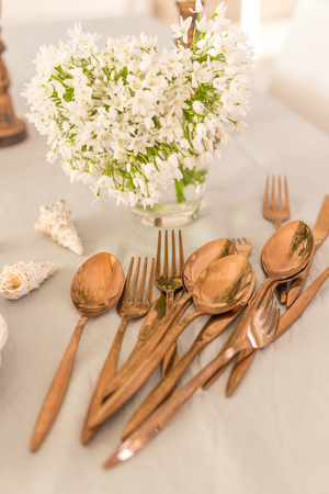 Vertical shot of copper color spoons and forks laid on linen tablecloth with seashells and white spring flowers blurred at far distance view.
