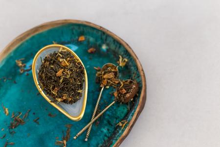 Disparo horizontal de un té de hierbas en una taza de cerámica y cucharaditas de oro colocadas en una placa de cerámica turquesa. Copie el espacio. Foto de archivo