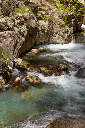 Vertical shot of a powerful water stream in the mountain river canyon with crystal clear water. 免版税图像