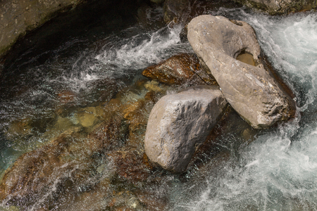 Closeup shot of powerful water stream in the mountain river. 免版税图像