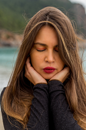Closeup portrait of a beautiful female with bold makeup, eyes closed and wind in the hair