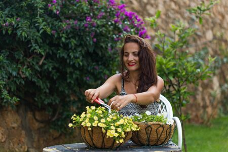 Horizontal portrait of a brunette toddler girl wearing summer outfit and cutting white calibrachoa flowers. Copy space. Stock fotó