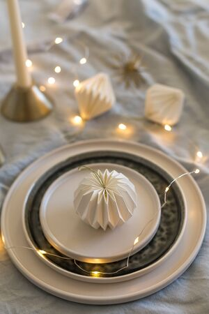 Vertical shot of monochrome Christmas table setting with Christmas lights and white origami decorations