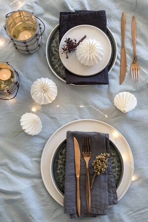 Vertical shot of Christmas table setting with black and white stoneware, lights and candles placed over light gray washed linen tablecloth