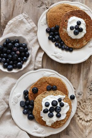 Healthy breakfast concept. Oatmeal pancakes topped with yogurt and blueberries