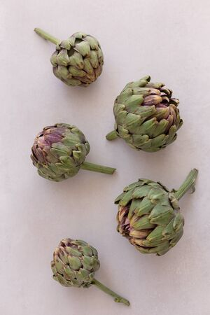 Topview image of artichokes on a light gray background.