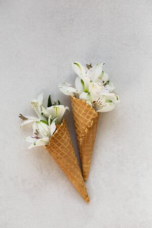 Summer concept. Ice-cream cone with white flowers in it.