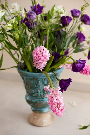 Bouquet of pink hyacinthus and purple lisianthus in a turquoise
