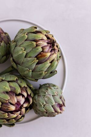 Topview image of artichokes in a white plate over light gray bac