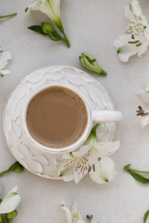 Morning coffee with flowers over light gray tabletop.