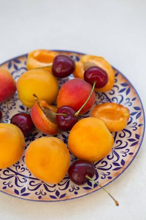 Apricots and cherries on a ceramic plate