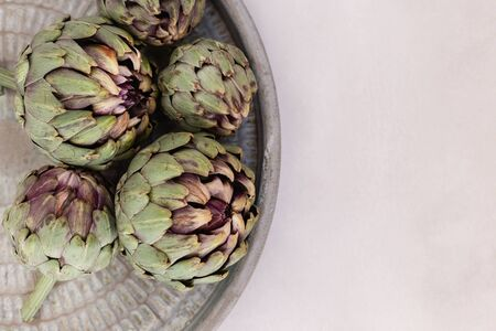 Topview image of artichokes in a rustic metal tray. Horizontal composition. Negative space. 版權商用圖片