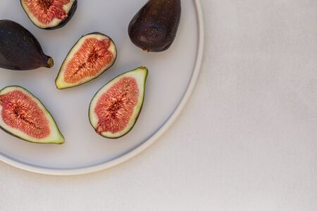 Top view of figs on white ceramic plate.