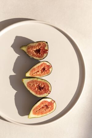 Topview image of figs in white ceramic plate. Negative space.