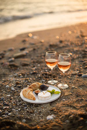 Vertical image of the  romantic beach picnic for two at sunset with two glasses of rose wine, croissants, camamber cheese and figs. Negative space. 版權商用圖片