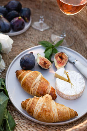 Vertical image of croissants, figs and camamber cheese in a minimalistic white plate. 版權商用圖片