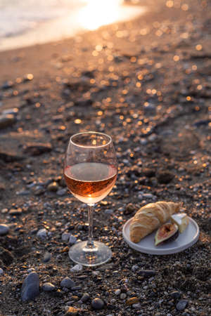 A glass of rose wine on the beach served with croissants and figs. Negative space. Shallow depth of field.