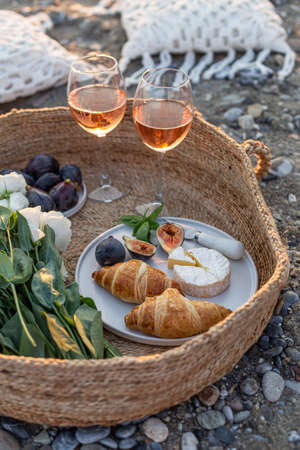 Vertical image of the outdoor picnic with wine, figs, croissants and camamber cheese in a woven basket.