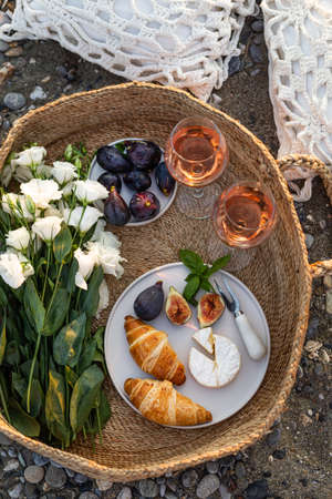 Upper view image of an outdoor picnic with wine, croissants, camamber cheese, figs and lisianthus flowers in a woven basket