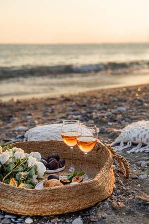 Vertical image of the beach picnic with wine, figs, croissants and camamber cheese in a woven basket. Negative space. 版權商用圖片
