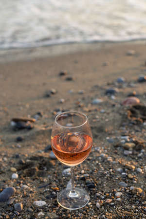 Vertical image of a glass of rose wine on the sand and pebble beach. Negative space.